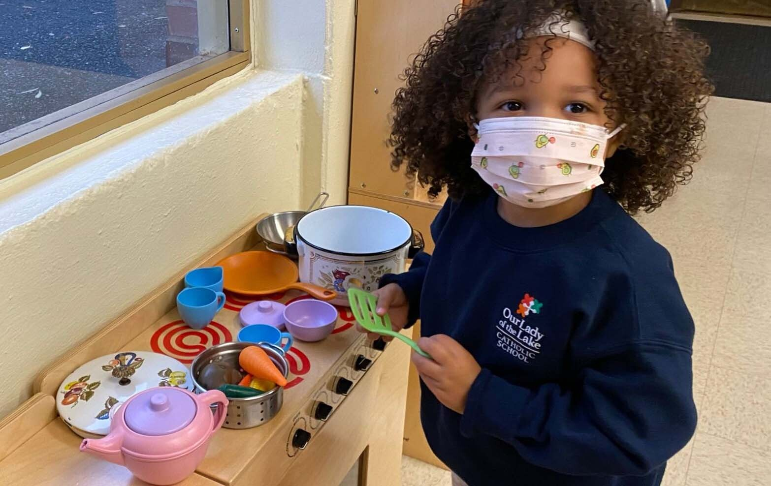 Preschool student in a play kitchen